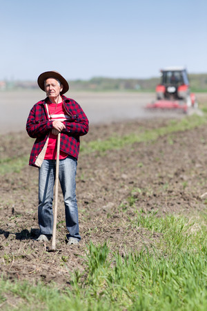 Senior peasant with hoe standing on farmland, tractor in background