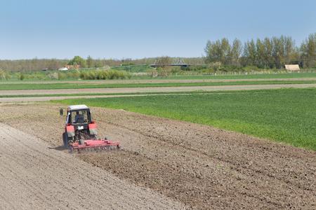 arando: Paisaje rural de tractor arando la tierra fértil cerca del pueblo Foto de archivo