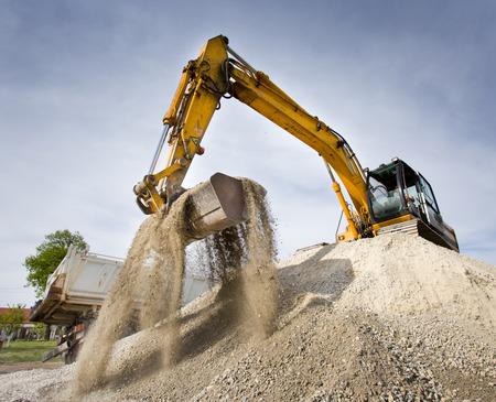 maquinaria pesada: Excavadora de pie en la cima de la colina de grava y gravilla en movimiento con la cucharada