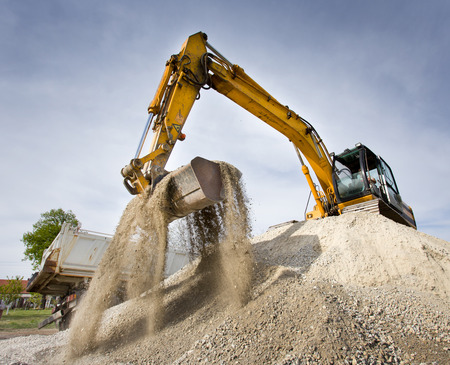 heavy equipment: Excavator standing on top of gravel hill and moving gravel with scoop Stock Photo