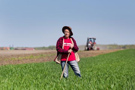 campesino: Campesina mayor con el azad�n en pie en tierras de cultivo, tractor en el fondo Foto de archivo
