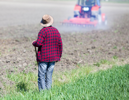 back hoe: Rear view of farmer with hoe standing on fertile land and looking at tractor plowing soil Stock Photo