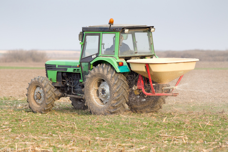 agronomic: Tractor fertilizing farmland on cloudy day in springtime Stock Photo