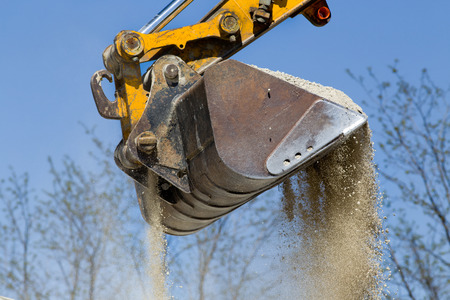 dredging tools: Close up of excavator bucket scooping gravel from pile for road construction Stock Photo