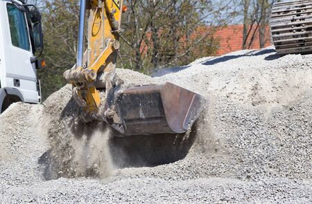 bagger: Close up of excavator bucket scooping gravel from pile for road construction Stock Photo