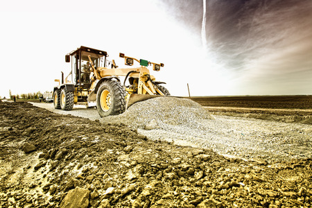 industrial sites: Grader leveling gravel on road construction site