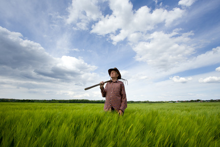 Old farmer carrying hayfork on shoulder and walking through green barley field in spring Archivio Fotografico