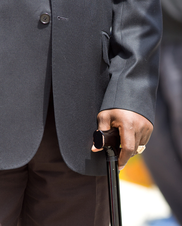 mafioso: Older man in black suit with big golden ring on finger walking with crutch