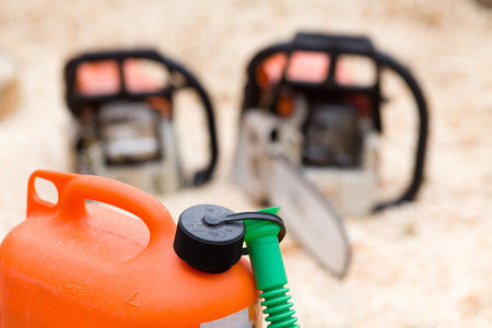 petrolium: Close up of orange plastic fuel canister with two chainsaws in background