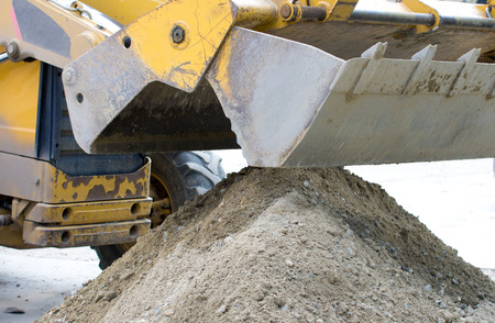 dredging tools: Close up of bulldoger bucket collecting sand on construction site Stock Photo