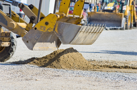 dredging tools: Close up of bulldozer bucket collecting sand on construction site in urban area
