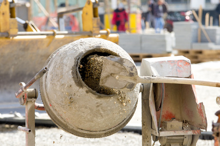 Close up of shovel throwing cement into concrete mixer on construction site