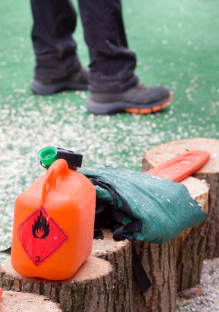 petrolium: Orange plastic fuel canister with chainsaw on stumps Stock Photo