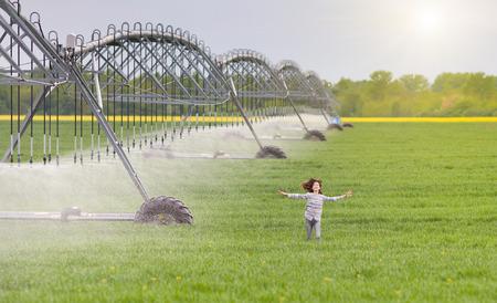 tierra fertil: Chica joven que se ejecuta con los brazos abiertos en la tierra f�rtil junto sistema de riego