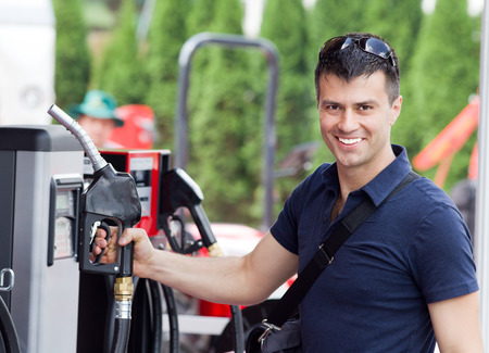 fueling: Happy young man holding fuel nozzle at gas station