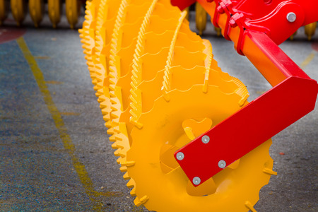 harrowing: Close up of new yellow agricultural connection machine for tractor