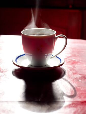 steaming: Cup of hot coffee steaming on the table early in the morning with long shadows