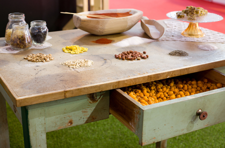a jar stand: Different spices and grains on piles and jars on old table