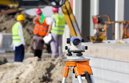 topografo: Topografía de medición de nivel de equipo de teodolito en el trípode en el sitio de construcción con los trabajadores en el fondo