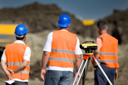 leveling instrument: Theodolite on tripod at road construction site with workers supervising works