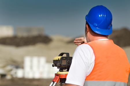 teodolito: Ingeniero topógrafo trabaja con el teodolito en el sitio de construcción de carreteras