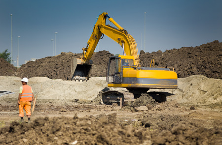 job site: Excavator digging and moving earth at construction site