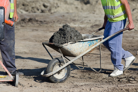construction man: Construction worker pushing barrow with concrete at building site