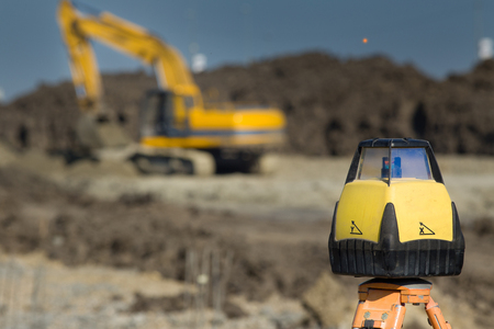 leveling: Rotating laser surveying equipment at road construction site with dredger in background