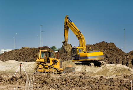 construction machines: Excavator and bulldozer working at big construction site Stock Photo