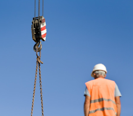 lifting hook: Close up of crane hook lifting weights against blue sky, worker blurred in forefront Stock Photo