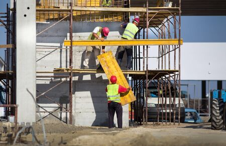 scaffolds: Team work at construction site, workers passing metal formworks on scaffolds Stock Photo