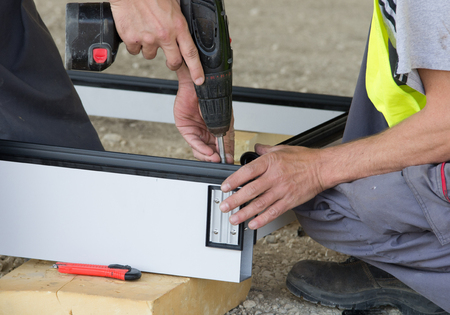 ventilated: Two construction workers assembling metal profiles with screwdriver drill for ventilated facade on the ground at building site