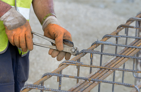 reinforcing bar: Close up of construction worker hands working with pincers on fixing steel rebar at building site Stock Photo