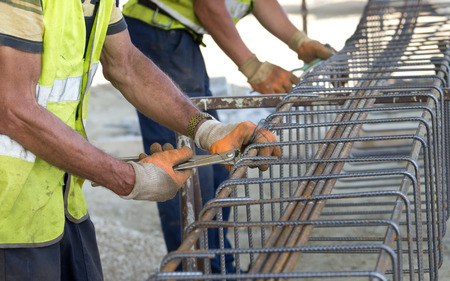 Close up of construction worker hands working with pincers on fixing steel rebar at building site Stock Photo