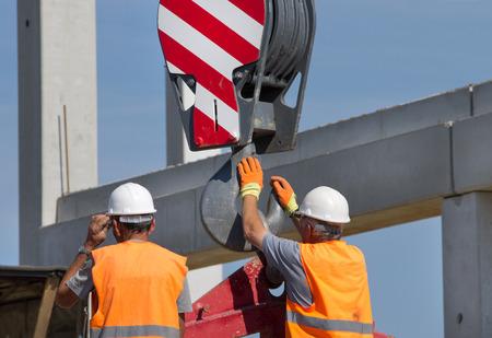 Operaio edile navigando con lastra di cemento armato sollevato da una gru in cantiere