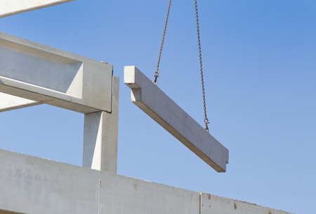 industrial sites: Crane lifting concrete truss for installing in building skeleton