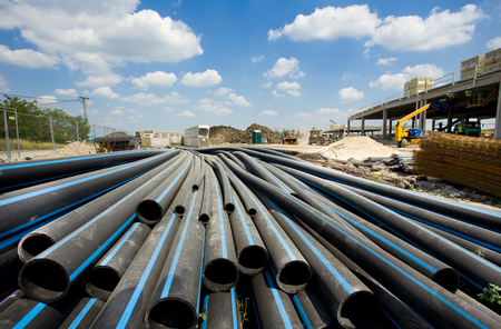 trenching: Pile of pvc pipes for underground cables and facilities at construction site