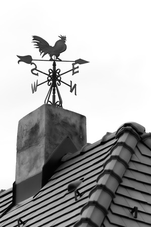 windward: Rooster weather vane on the roof with black tiles Stock Photo
