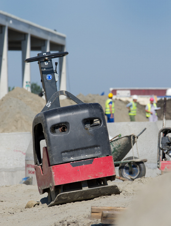 compaction: Vibratory plate compactor placed on sand slope at construction site