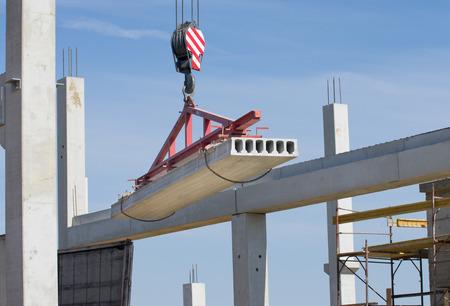 Concrete slab hanging from crane hook above building skeleton at construction site