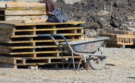 wheelbarrow: Old wheelbarrow standing next to wooden pallets at construction site Stock Photo
