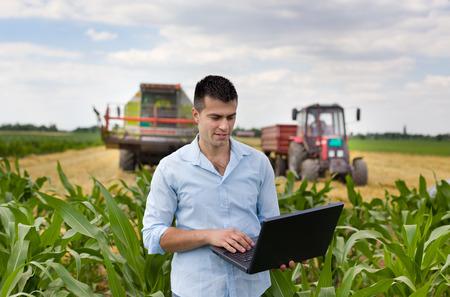 Aantrekkelijke jonge boer met laptop staan in maïsveld trekker en maaidorser werken in tarwe veld in de achtergrond