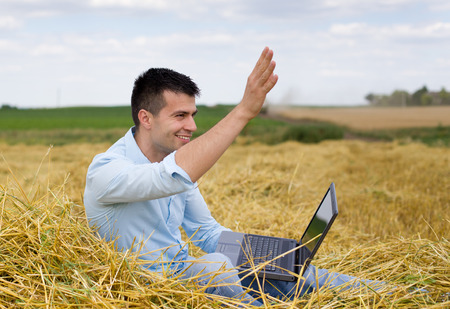 Young attractive man with laptop sitting on haystack at farmland and waving hand to someone photo