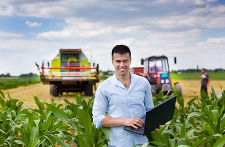 maiz: Agricultor atractiva joven con ordenador portátil de pie en el maíz tractor de campo y cosechadoras trabajando en campo de trigo en el fondo Foto de archivo