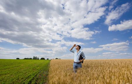 잘 익은 밀밭에 서서 비를 위해 하늘을 바라 보는 젊은 농부 스톡 콘텐츠