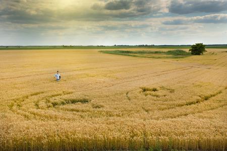 tierra fertil: Granjero que se coloca en la madura amplia vista campo de trigo de las tierras f�rtiles de las llanuras Foto de archivo