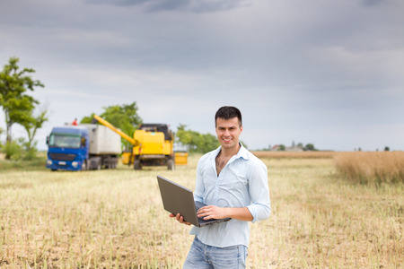 Young attractive farmer with laptop standing in rapeseed field truck and combine harvester working in the field in background