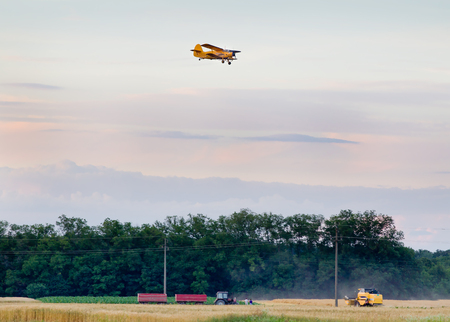 mosquitoes: Rural landscape of tractor and combine harvester working in field while airplane spraying mosquitoes Stock Photo