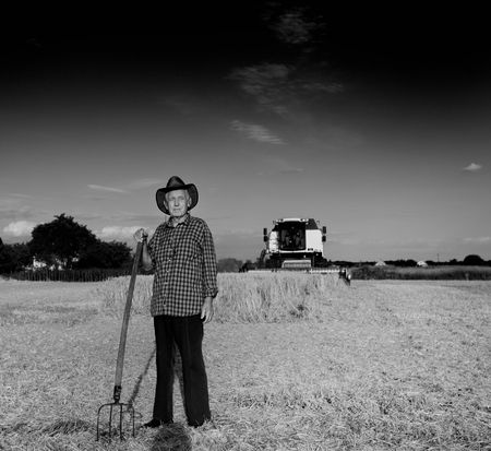 hayfork: Old farmer with hat and hayfork standing on field during harvest, combine harvester in background, black and white image Stock Photo