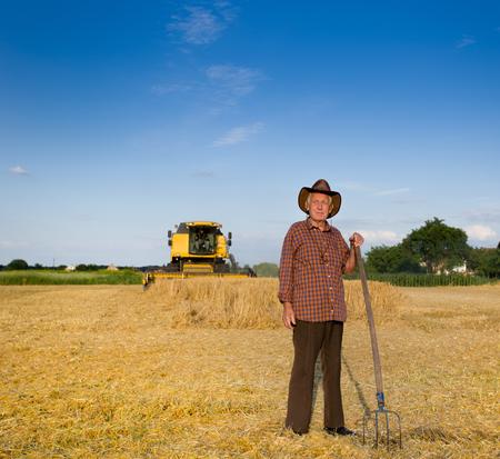 hayfork: Old farmer with hat and hayfork standing on field during harvest, combine harvester in background